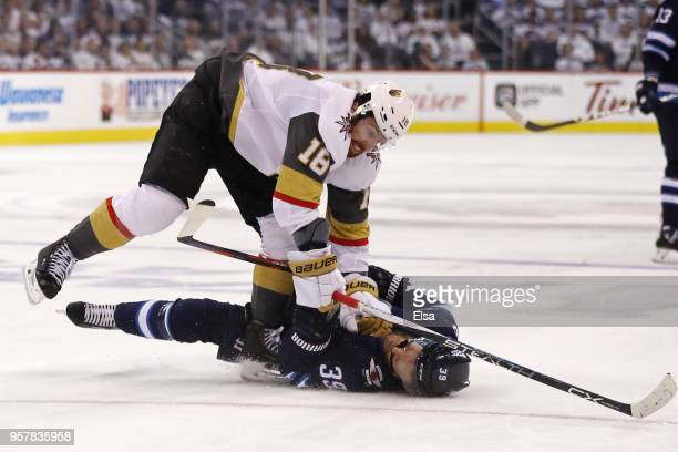 Toby Enstrom of the Winnipeg Jets is knocked down to the ice by James Neal of the Vegas Golden Knights during the second period in Game One of the...
