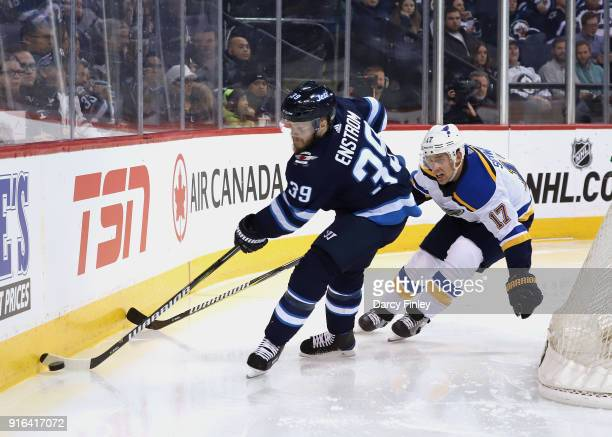 Toby Enstrom of the Winnipeg Jets plays the puck along the boards away from Jaden Schwartz of the St Louis Blues during third period action at the...