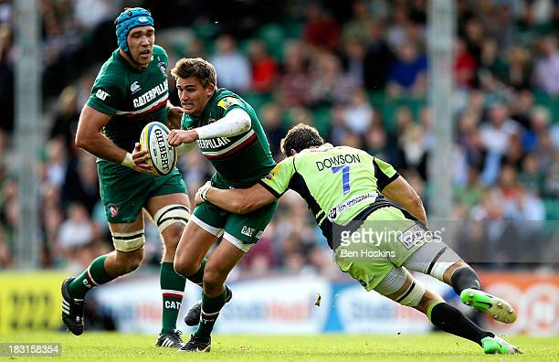 Toby Flood of Leicester is tackled by Phil Dowson of Northampton during the Aviva Premiership match between Leicester Tigers and Northampton Saints...