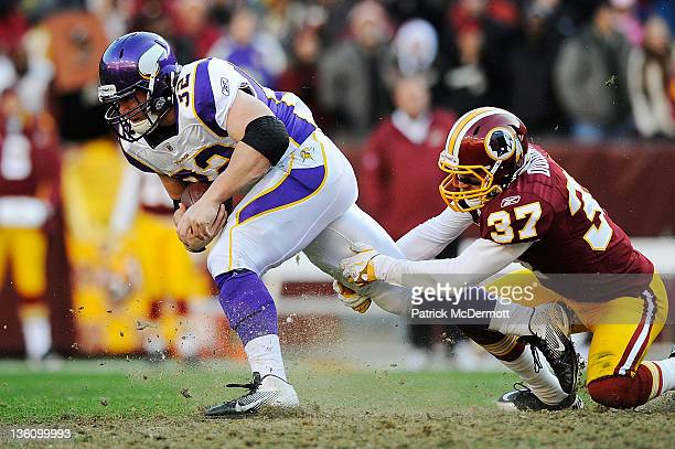 Toby Gerhart of the Minnesota Vikings breaks the tackle of Reed Doughty of the Washington Redskins during a game at FedExField on December 24 2011 in...