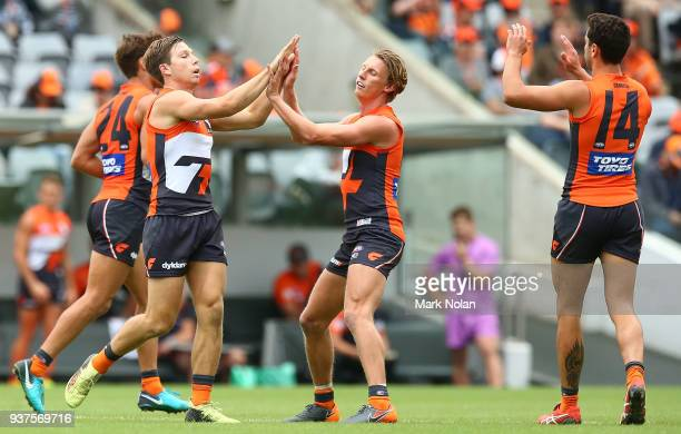 Toby Greene of the Giants celebrates kicking a goal with team mates during the round one AFL match between the Greater Western Sydney Giants and the...