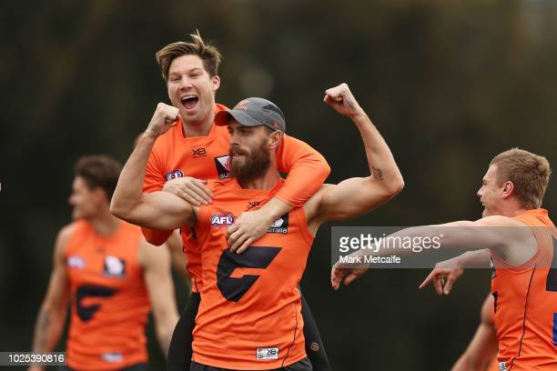 Toby Greene of the Giants celebrates with team mate Tim Mohr after victory in a training drill during a Greater Western Sydney Giants AFL training...