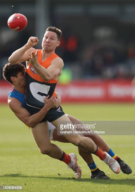 Toby Greene of the Giants handballs as he is tackled during the round 17 AFL match between Greater Western Sydney Giants and Gold Coast Suns at Mars...