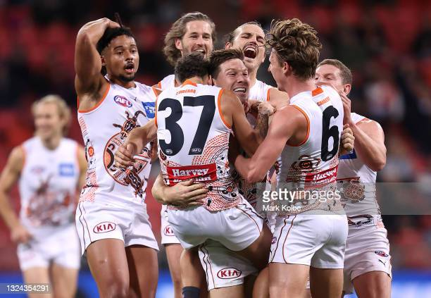 Toby Greene of the Giants is congratulated by team mates after kicking a goal during the round 14 AFL match between the Greater Western Sydney Giants...