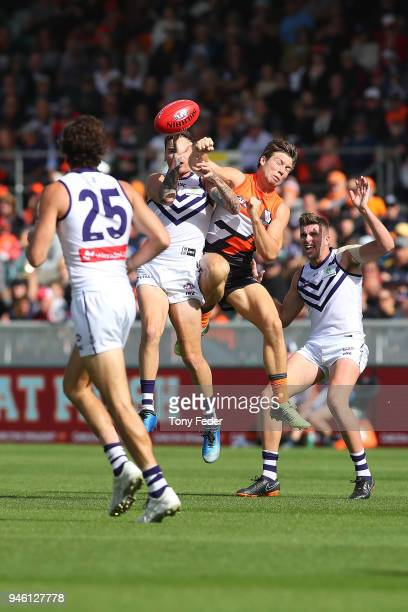 Toby Greene of the Giants punches the ball during the round four AFL match between the Greater Western Sydney Giants and the Fremantle Dockers at...
