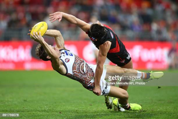 Toby Greene of the Giants takes a mark in front of Mark Baguley of the Bombers during the round 11 AFL match between the Greater Western Sydney...