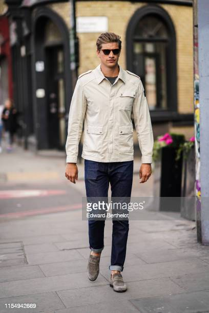 Toby HuntingtonWhiteley wears sunglasses a white jacket denim jeans gray suede shoes during London Fashion Week Men's June 2019 on June 09 2019 in...