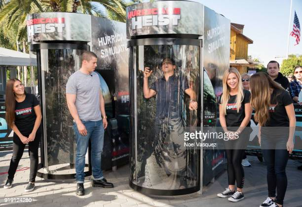 "Toby Kebbell watches Mario Lopez enter the Hurricane Heist simulator ""Extra"" at Universal Studios Hollywood on February 16, 2018 in Universal City,..."