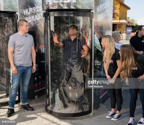 Toby Kebbell watches Mario Lopez enter the Hurricane Heist simulator 'Extra' at Universal Studios Hollywood on February 16 2018 in Universal City...