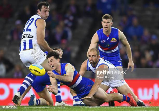Toby McLean of the Bulldogs handballs whilst being tackled by Ben Cunnington of the Kangaroos during the round 14 AFL match between the Western...
