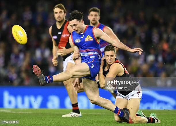 Toby McLean of the Bulldogs kicks whilst being tackled by Orazio Fantasia of the Bombers during the round 19 AFL match between the Western Bulldogs...
