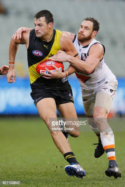 Toby Nankervis of the Tigers is tackled by Shane Mumford of the Giants during the round 18 AFL match between the Richmond Tigers and the Greater...