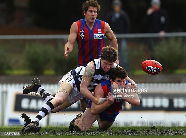 Toby Pinwill of Port Melbourne handballs whilst being tackled by Mitchell Cuthill of Geelong during the round 17 VFL match between Port Melbourne and...