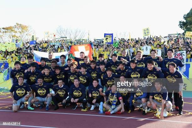Tochigi SC players and staffs pose for photographs with supporters as they celebrate the promotion to the J2 after the JLeague J3 match between Azul...