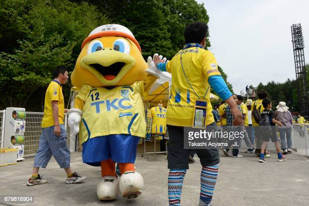 Tochigi SC supporter high fives with a mascot 'Mamorukun' prior to the JLeague J3 match between Tochigi SC and Giravanz Kitakyushu at Tochigi Green...
