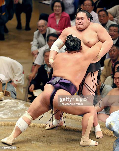 Tochiozan pushes Mongolian ozeki Terunofuji out of the ring to win during day twelve of the Grand Sumo Autumn Tournament at Ryogoku Kokugikan on...
