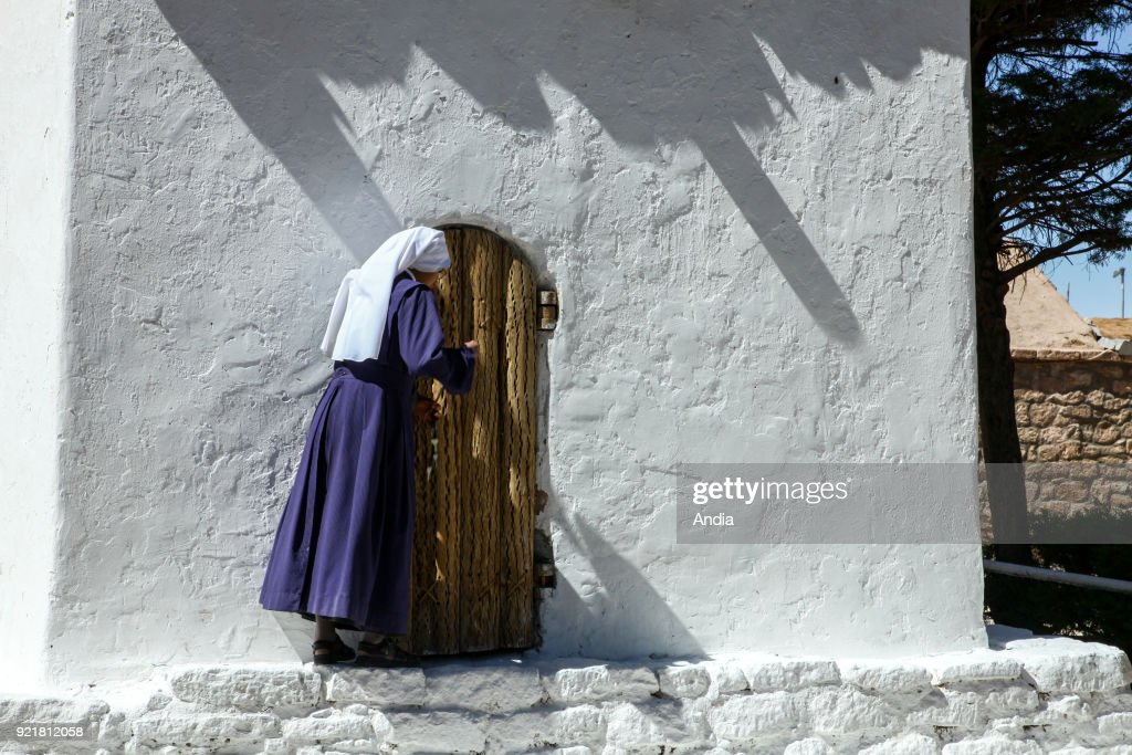 oasis village of Toconao in the Atacama desert, with its picturesque church. Nun at the entrance to the church.