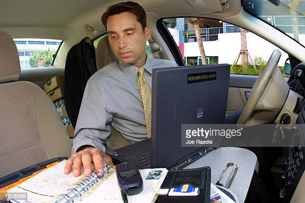 Todd Amrhein a pharmaceutical salesman uses his car as an office June 15 2001 in Miami FL Amrhein uses a desk customized for car use as well as a...
