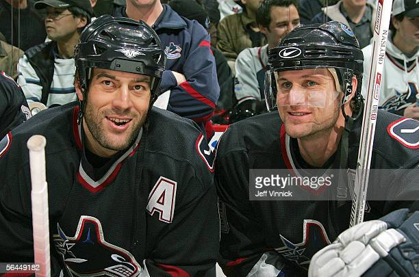 Todd Bertuzzi and Markus Naslund of the Vancouver Canucks share a laugh as they sit on the bench during their game against the Edmonton Oilers at...