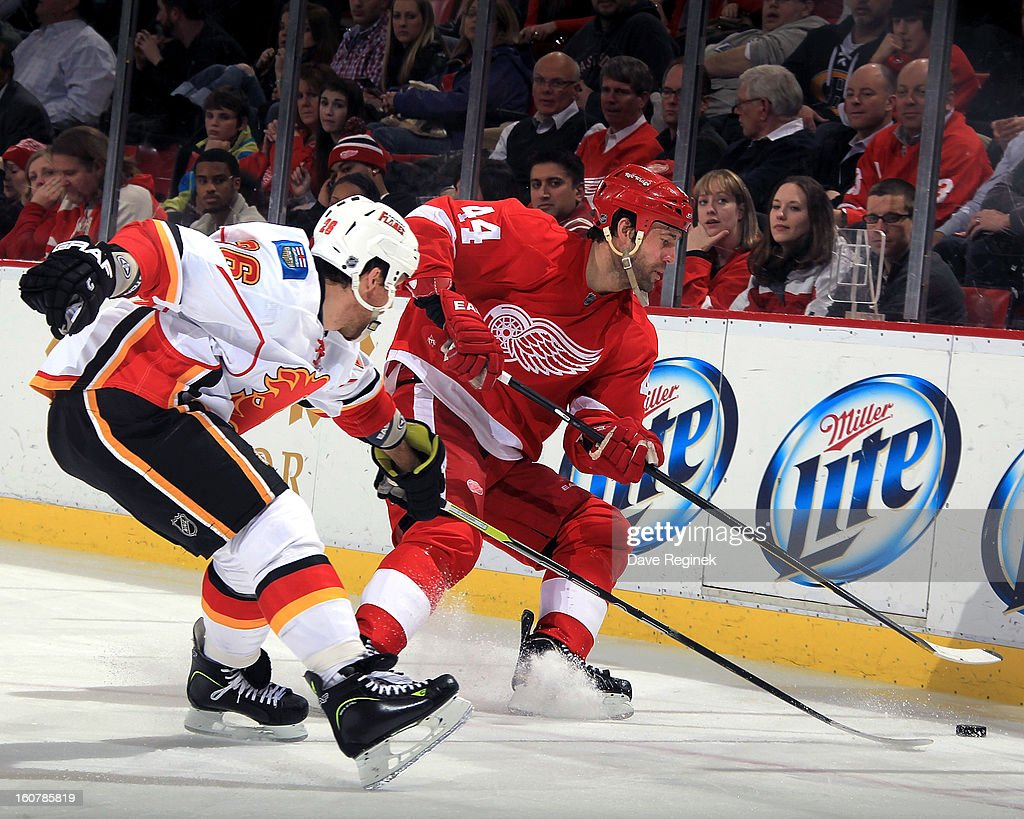 Todd Bertuzzi #44 of the Detroit Red Wings and Dennis Wideman #26 of the Calgary Flames battle for the puck along the boards during a NHL game at Joe Louis Arena on February 5, 2013 in Detroit, Michigan. Calgary defeated Detroit 4-1
