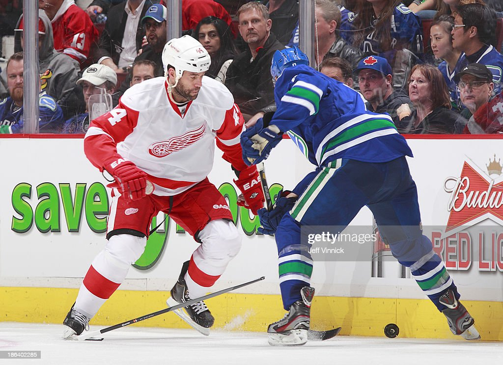 Todd Bertuzzi #44 of the Detroit Red Wings breaks his stick as he plays the puck around Christopher Tanev #8 of the Vancouver Canucks during their NHL game at Rogers Arena on October 30, 2013 in Vancouver, British Columbia, Canada. Detroit won 2-1.