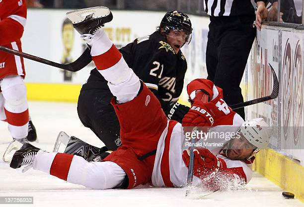 Todd Bertuzzi of the Detroit Red Wings falls while skating the puck against Loui Eriksson of the Dallas Stars at American Airlines Center on January...