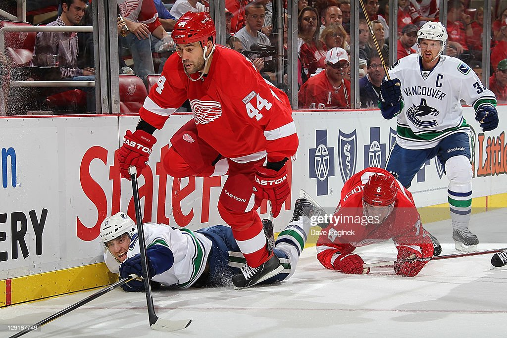 Todd Bertuzzi #44 of the Detroit Red Wings gets tripped up by Christopher Tanev #8 of the Vancouver Canucks during an NHL game at Joe Louis Arena on October 13, 2011 in Detroit, Michigan.