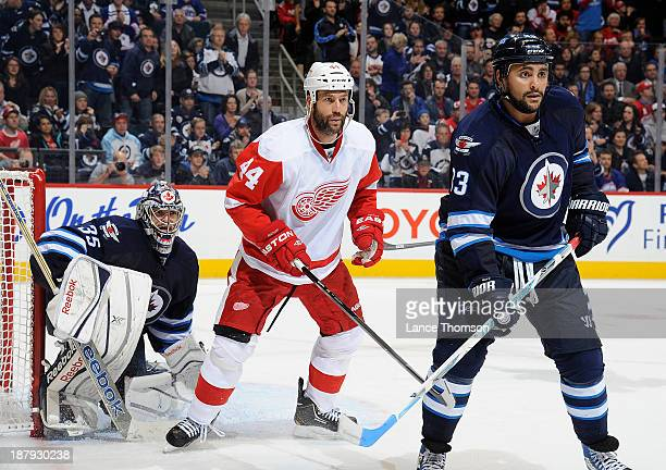 Todd Bertuzzi of the Detroit Red Wings positions himself between goaltender Al Montoya and Dustin Byfuglien of the Winnipeg Jets during thirdperiod...