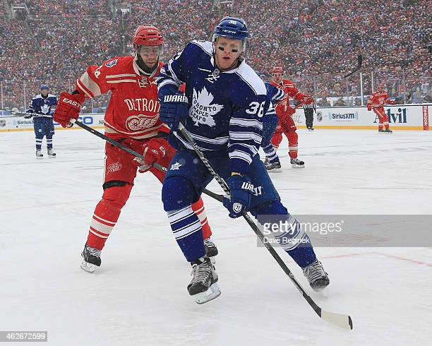 Todd Bertuzzi of the Detroit Red Wings skates after a loose puck against Carl Gunnarsson of the Toronto Maple Leafs during the Bridgestone NHL Winter...