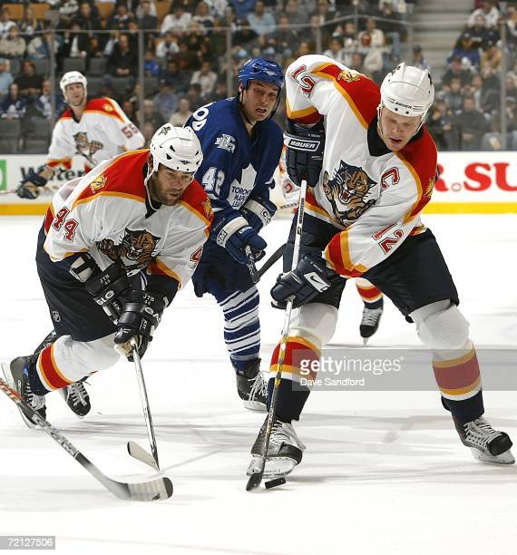Todd Bertuzzi of the Florida Panthers is tripped up by Kyle Wellwood of the Toronto Maple Leafs as Olli Jokinen of the Florida Panthers caries the...