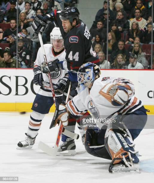 Todd Bertuzzi of the Vancouver Canucks attempts to redirect a shot against goaltender Jussi Markkanen and Marc-Andre Bergeron of the Edmonton Oilers...