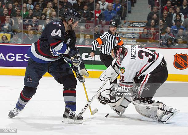Todd Bertuzzi of the Vancouver Canucks chips the puck between the legs of goaltender Craig Anderson of the Chicago Blackhawks for the Canuck's second...