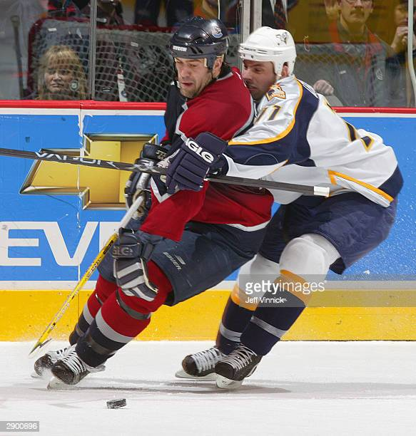 Todd Bertuzzi of the Vancouver Canucks is held in check by David Legwand of the Nashville Predators during the third period of their NHL game at...