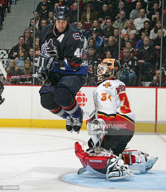 Todd Bertuzzi of the Vancouver Canucks jumps in the air in front of goaltender Miikka Kiprusoff of the Calgary Flames as the Canucks score at General...