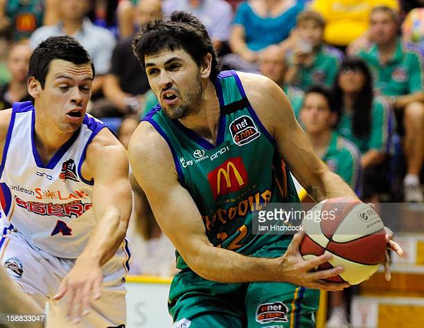 Todd Blanchfield of the Crocodiles attempts to drive past Jason Cadee of the 36ers during the round 12 NBL match between the Townsville Crocodiles...