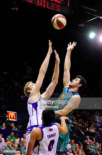 Todd Blanchfield of the Crocodiles takes a shot over Luke Schenscher of the 36ers during the round 12 NBL match between the Townsville Crocodiles and...