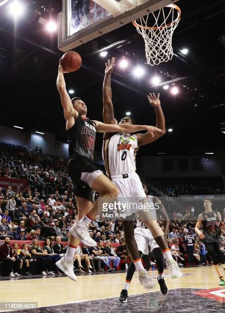 Todd Blanchfield of the Hawks drives to the basket under pressure from Cameron Oliver of the Taipans during the round two NBL match between the...