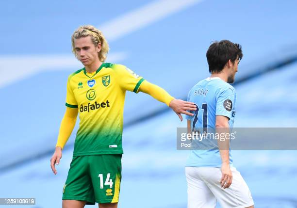 Todd Cantwell of Norwich City congratulates David Silva of Manchester City as he leaves the field on his final appearance for Manchester City during...
