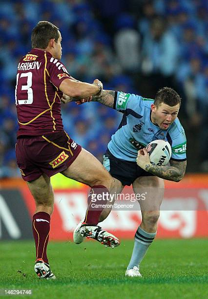 Todd Carney of the Blues fends off Ashley Harrison of the Maroons during game two of the ARL State of Origin series between the New South Wales Blues...