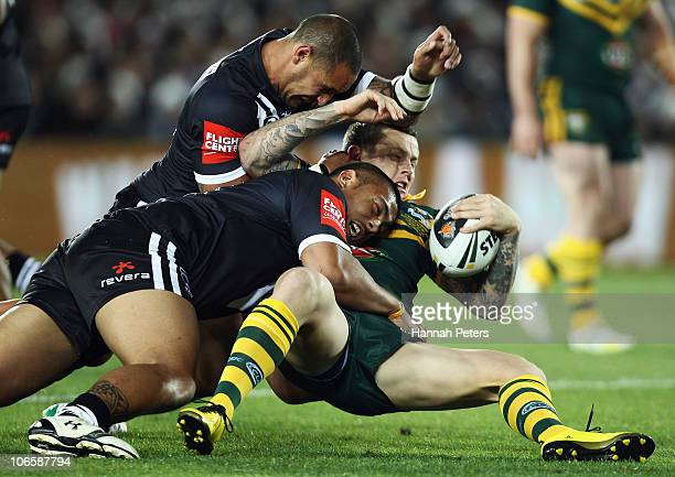 Todd Carney of the Kangaroos is taken down by Sika Manu and Jeremy Smith of the Kiwis during the Four Nations match between the New Zealand Kiwis and...