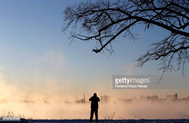 Todd Chase of Gorham takes photos of the city skyline emerging from sea smoke over Back Cove at sunrise on Tuesday during singledigit weather Chase...