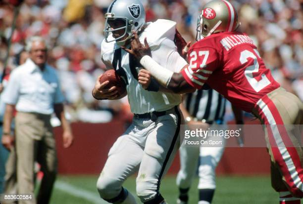 Todd Christensen of the Los Angeles Raiders fights off the tackle of Carlton Williamson of the San Francisco 49ers during an NFL football game...