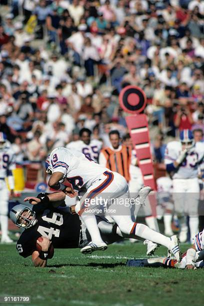 Todd Christensen of the Los Angeles Raiders is tackled by Dennis Smith of the Denver Broncos during the game at the Los Angeles Memorial Coliseum on...