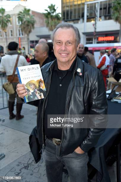 """Todd Fisher, brother of the late actress Carrie Fisher, poses with his book """"My Girls"""" at the IMAX opening of """"Star Wars: The Rise Of Skywalker"""" at..."""
