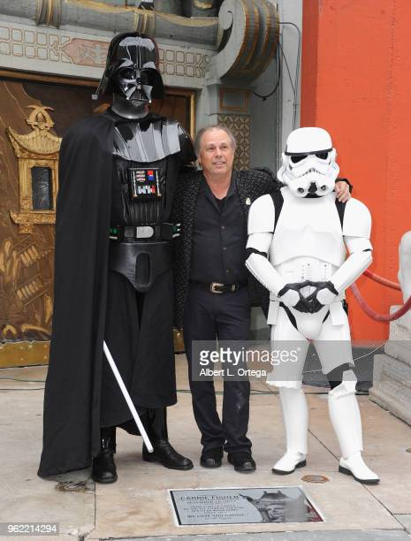 Todd Fisher Darth Vader and a Storm Trooper pose beside the etched granite plaque for the late Carrie Fisher unveiled in front of the TCL Chinese...