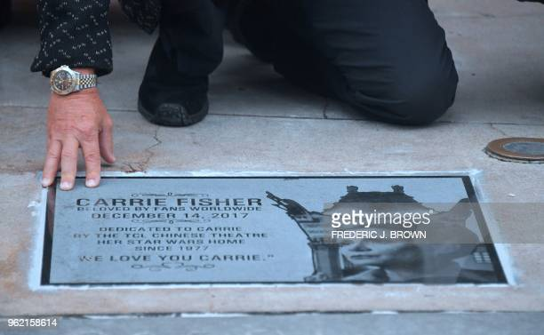 Todd Fisher looks at the etched granite plaque for his sister the late Carrie Fisher unveiled in front of the TCL Chinese Theater on May 24 2018 in...
