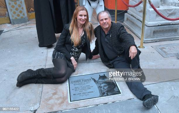 Todd Fisher poses with Alwyn Hight Kushner president and COO of the TCL Chinese Theater beside the etched granite plaque for his sister the late...