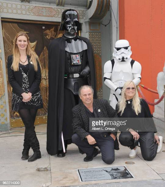 Todd Fisher poses with Alwyn Hight Kushner president and COO of the TCL Chinese Theater Darth Vader and a Storm Trooper beside the etched granite...