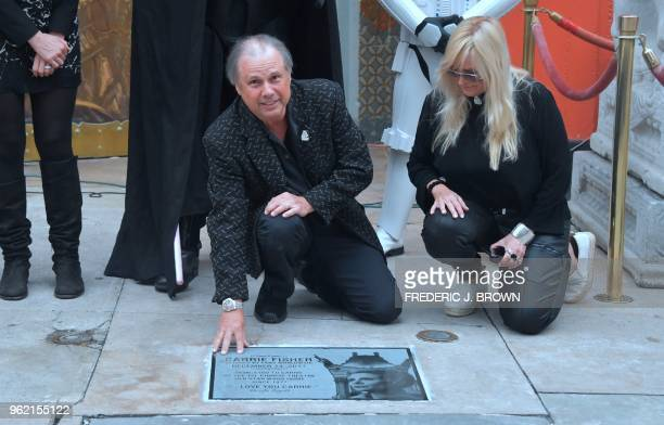 Todd Fisher poses with the etched granite plaque for his sister the late Carrie Fisher unveiled in front of the TCL Chinese Theater on May 24 2018 in...