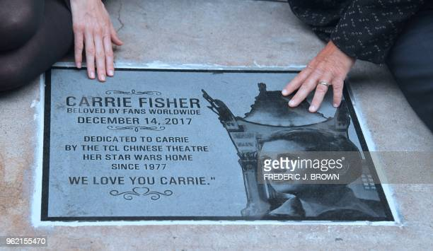 Todd Fisher with Alwyn Hight Kushner president and COO of the TCL Chinese Theatertouch the etched granite plaque for his sister the late Carrie...